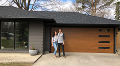 homeowners standing in front of garage door